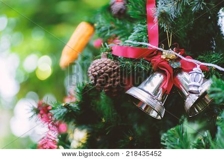 Christmas jingle bell and pine cone decoration on pine tree branch
