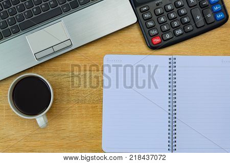 Laptop Computer Or Notebook, Calculator And Cup Of Coffee On Working Table With Copy Space Top View.