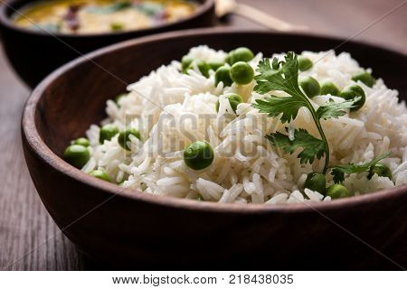 Basmati Rice Pilaf or pulav with Peas, or vegetable rice using green peas also known as matar pulav, served with plain dal
