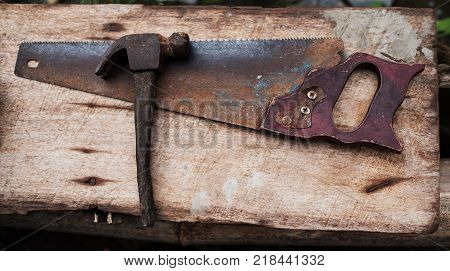 Old rusty tools hammer and hand saw for carpenter work