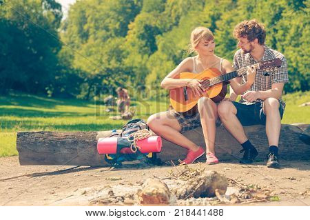 Adventure tourism enjoying summer time together - young couple tourists having fun playing guitar in camping outdoor