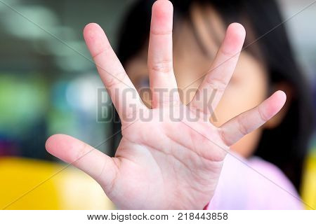 Asian child girl raised his hand to block or making stop gesture
