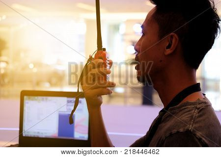 Man with a Walkie Talkie or Portable radio transceiver for communication at event poster