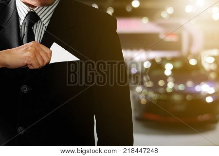 Businessman in suit is taking a credit card out of a shirt to buy a producton an abstract background blurred car The concept of spending wisely