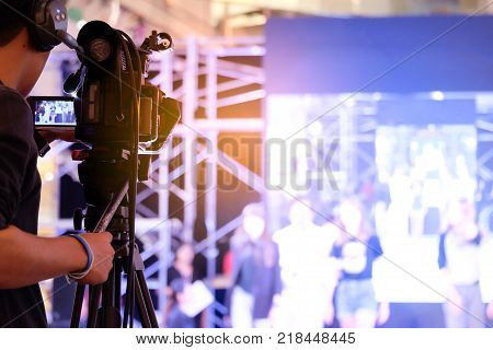 Videographer video recording activity within the event on Stage