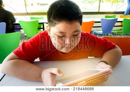 Asian child Boy are addictive playing tablet and mobile phones Game Addiction