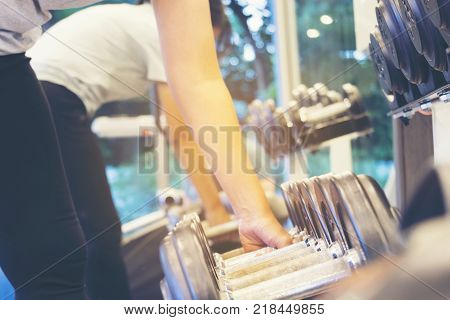 Fitness Woman Lifting Weight for Exercise in Gym Selective focus on Weight Handle