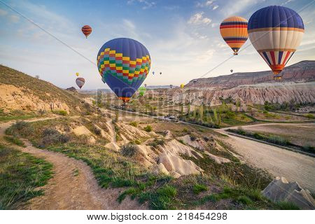 Flying on the balloons early morning in Cappadocia. Colorful sunrise in Red Rose valley Goreme village location Turkey Asia. Artistic style post processed photo.