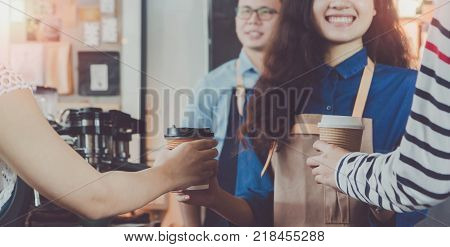 Young beautiful Asian woman barista wear brown apron holding hot coffee cup served to customer at bar counter in coffee shop with smile face.Concept of cafe and coffee shop small.