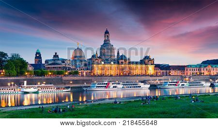 Evennig view of Academy of Fine Arts and Baroque church Frauenkirche cathedral. Colorful sunset on Elbe river in Dresden Saxony Germany Europe. Artistic style post processed photo.