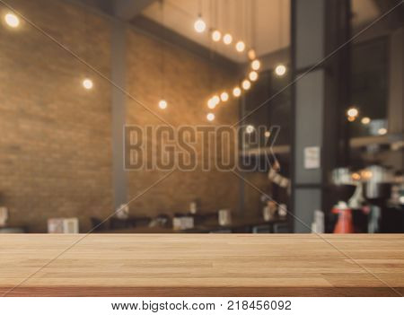 Wood table top and blurred bokeh cafe and coffee shop interior background with vintage filter - can used for display or montage your products.
