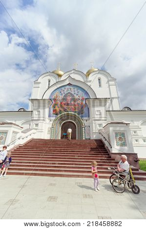 Yaroslavl, Russia. - June 3.2016. Photo of the Assumption Cathedral from near the wide-angle lens. At the entrance, a disabled person without legs, sitting in a stroller, collects alms.