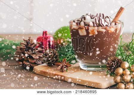 Hot chocolate in glass cup topping with marshmallow and dark chocolate sauce. Homemade hot cacao or chocolate on wood table in side view copy space with Christmas theme and snowfall background. Hot chocolate in concept to present Christmas drink.