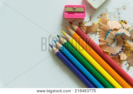 Stationery set for drawing on white background include crayons ruler eraser sharpener and debris from the sharpening