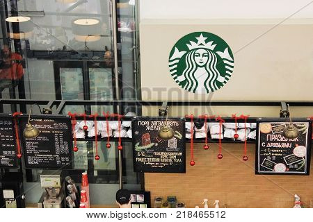 ST. PETERSBURG, RUSSIA - DECEMBER 9, 2017: Starbucks Coffee Shop Interior. Shop Front with Company Logo and Menu Decorated for Christmas Holidays. Starbucks is an American Coffee Shop Famous Worldwide