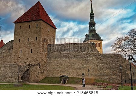 The tourists are taking photos of the wall surrounding the medieval old town of Tallinn the capital of Estonia. In the background there is the tower of the St. Nicholas Church.