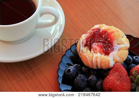 Breakfast platter filled with delicious seasonal fruit and pastries, hot cup of coffee on the side.