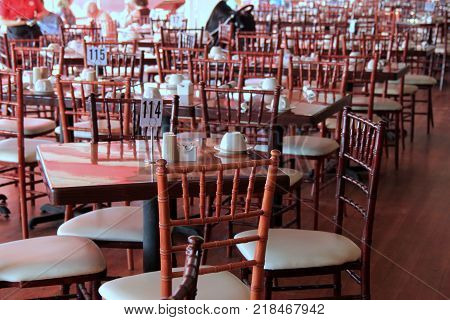 Dining area set with several wood tables and chairs on outdoor patio of restaurant.