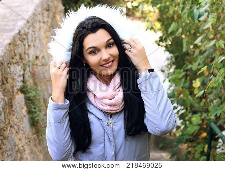 Beautiful young woman wearing winter coat with the faux - fur hood