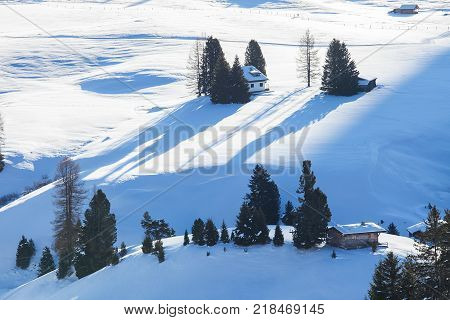Wooden mountain chalets with a view on the Langkofel and Plattkofel Sassolungo and Sassopiatto dolomites mountains at the Alpe di Siusi or Seiser Alm in South Tyrol Dolomites Italy in winter.