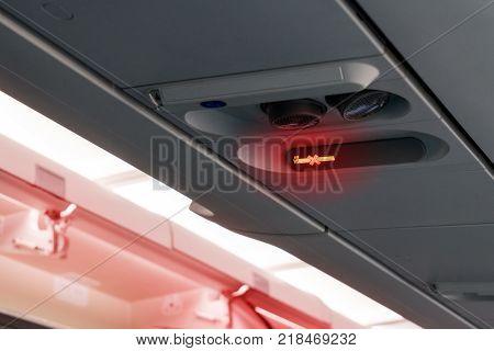 Warning of smoking ban or no smoking flight sign on airplane. Inflight smoking non smoking concept.