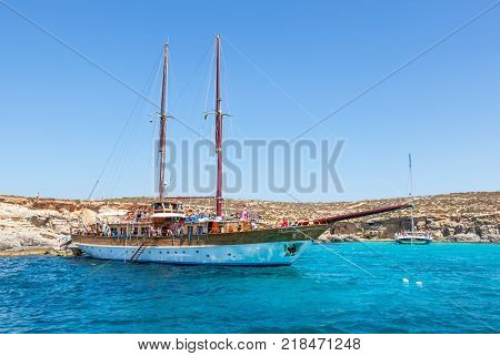 BLUE LAGOON MALTA - JUNE 25 2012: A schooner loaded with tourists moored at the Blue Lagoon in Malta.