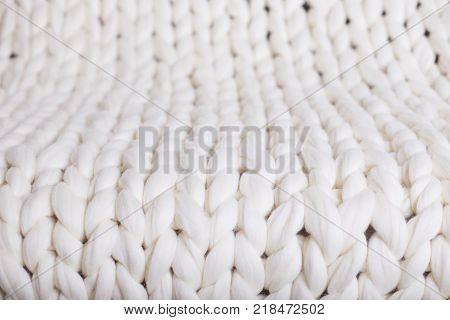 The texture of fabric thick beige sweater close-up. Knitted texture background. white plaid big knit. texture pigtail knitted blanket