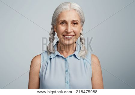 Senior Attractive Female With Pleased Expresssion, Has Broad Shining Smile, Grey Hair Tied In Two Pi