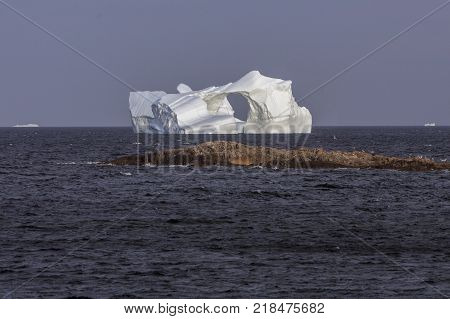 large iceberg with hole in middle near Fogo Island, Newfoundland, Canada