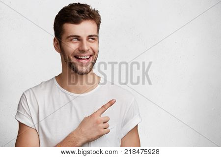 Emotional Happy Bearded Man In Casual Clothes Points At Copy Space, Being Surprised To Recieve New O