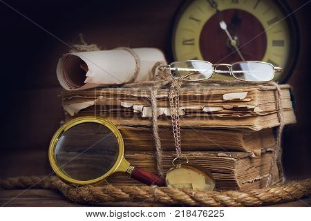 a still life with old scruffy books reading glasses, a clock and a magnifying glass on a dark background