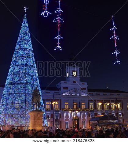 Madrid, Spain - December 12, 2017. Puerta del Sol square at nightfall illuminated by christmas lights and a shinny christmas tree with Real Casa de Correos in background. Madrid, Spain.