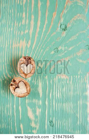 Two halves of walnut as heart are lying on light green painted textured wooden table with stripes and squiggly stains and copy space. Top view.