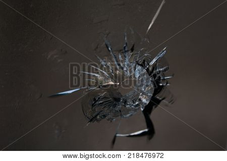 Broken glass. Hole cracks in the window from the fragment of the projectile. Background texture