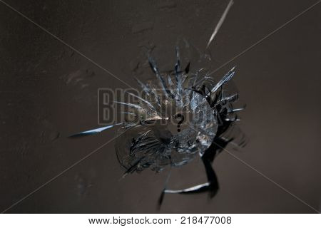 Broken glass. Hole cracks in the window from the fragment of the projectile. Background texture. A symbol of a broken life. How to live after you broke down