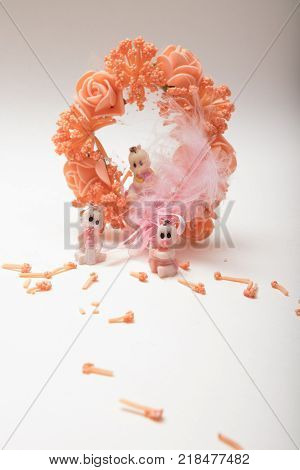 Three  baby dolls sitting around  a artificial fancy flower wreath with pink feather  on white background with copy space