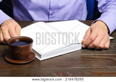 Male hand holding notepad or book with white clean pages black coffee in brown cup red pencil on dark wood working table working or study concept.