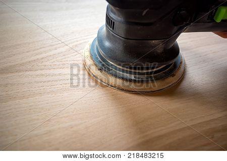 Close-up of man sanding a wood with orbital sander in woodwork workshop