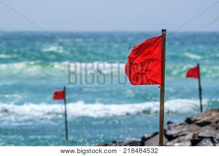 Red warning flag on beach showing that swimming is dangerous or prohibited