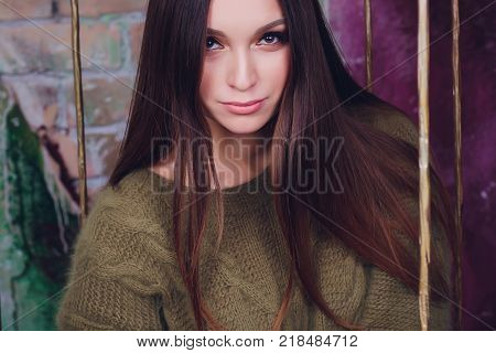 Beautiful girl in green sweater is sitting on big cozy carpet and holding boxes of gifts for her beloved. covered sits in a cage