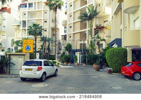 Rishon LeZion, Israel-April 26, 2015: Inside semicircle courtyard of condominium complex located at Ha-Botsrim Street. Contemporary multi-story residential buildings are enclosed it. There are white and red cars in the foreground. Bright sunny day.