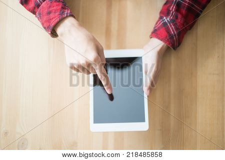 Cropped view of person using touchpad and sitting at table. Top view.