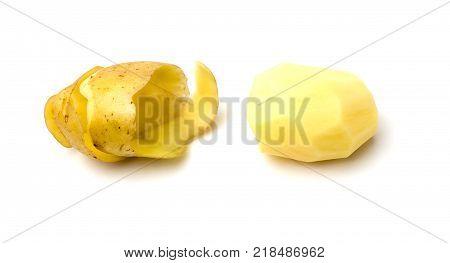 Peeled potatoes on a white background. Raw peeled potatoes and peelings close-up.