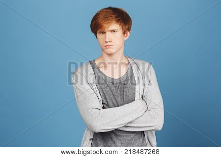 Close up of unhappy young good-looking ginger boy in casual stylish outfit crossing hands, looking in camera with offended and unsatisfied face expression, after argument with girlfriend