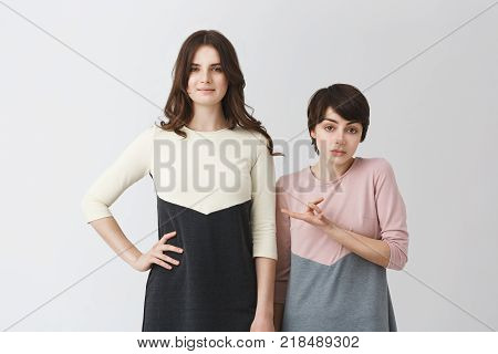 Funny portrait of pair of young student girls in matching clothes. Long-haired girl being taller than her short girlfriend