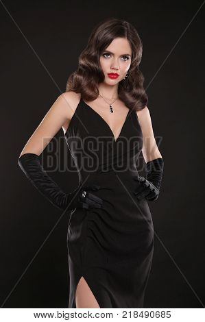 Fashionable model. Elegant lady in long sexy dress with retro wavy hairstyle posing isolated on studio black background. Beautiful brunette woman in glamour gloves. Fashion style photo.