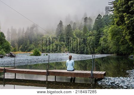 Woman Sits on Simple Wooden Footbridge over calm mountain river