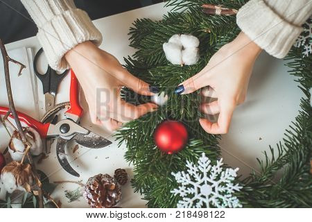 Cute Florist Woman Making Christmas Wreath with Glass Balls Snowflake and Green Xmas Tree at Home Office Desk. Florist's Workplace