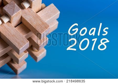 2018 goals on blue background and wooden barin teaser, Targets, goal, dreams and New Year's promises for the next year.