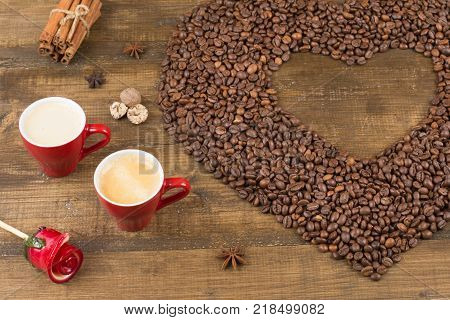 Two cups of coffee with a foam top view. Coffee beans badon cinnamon and caramel on a wooden surface. Love of a coffee drink. Morning invigorating coffee for two. Heart made of coffee beans